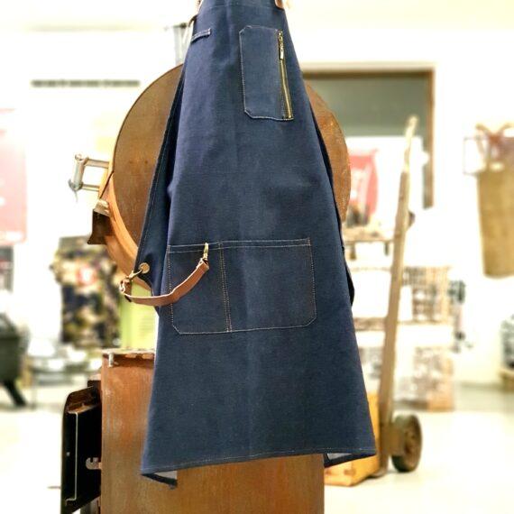Köksförkläde i grovt jeanstyg och läder Ett snyggt köksförkläde i rejält jeanstyg som hänger snyggt. Remmar i äkta läder tillsammans med bronsfärgade spännen och öljetter ger en tidlös och klassik look. Blir bara snyggare och snyggare med lite slitage och patina. Mobilficka på bröstet. Genom att förlänga midjeremmen med den medföljande kedjan (vid en av öljetterna) kan man få det att passa oavsett midjans omkrets. Går att tvätta i maskin på skonsamt program (ta bort läderremmar som är löstagbara). Längd 88cm och vikt på nästan ett halvt kilo.