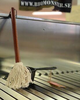 Såsmopp Sauce mop - Basting mop - klassisk USA-modell av grillpensel Sauce mop såsmopp bbq mop bastin mop basting mop bbq brush mop Ta en titt på denna ikoniska sauce mop - som tagen ur ett Hickory-rökigt avsnitt av BBQ-pitboys. Visst är det lättare att rengöra silikon än bomull men inget kan ersätta bomullstrådarnas förmåga att suga upp vätska. Långt skaft för att undvika brännskador och en läderrem för att kunna hänga upp ditt nya favoritredskap för att såsa till dina ribs. 33 cm långt skaft högkvalitativ bomull snyggt träskaft