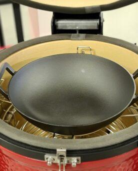 Wokpanna i gjutjärn För Kamado, grill eller spis Inkluderar 2 lock och underlägg Denna wokpanna passar perfekt att hänga i tillbehörsringen som följer med en Kamado Joe men kan även ställas direkt på ett galler i valfri kamado, och passar även på alla former av spisar. I paketet medföljer inte bara ett lock utan två - ett i glas som kan användas vid upp till 230 grader, ett annat som är gjort för att vara ett smidigt lock vid servering (det kan ju hänt förr att någon tagit tag i ett upphettat lock...eller?). Som lök på laxen medföljer även ett matchande underlägg av trä. En förutsättning för en krispig wok är att grönsaker (oftast frysta) tillagas med hög värme för att undvika att grönsakerna kokas - vilket skapar en helt annan rätt. Att använda en intensivt glödande kolbädd som värmekälla ger dig de bästa förutsättningarna, med en wok i gjutjärn tar du det i mål! Ju grövre gods desto mer energi kan lagras i metallen. När du lägger i frysta grönsaker kommer en betydande mängd energi (värme) stjälas från godset. Är godset för tunt blir det snabbt kallt och grönsakerna blir istället kokta i sin egen vätska eftersom att värmen inte räcker till för att få vätskan att avdunsta. Därför är det gjutjärn en stor skillnad när det exempelvis gäller en frusen wok-mix, detta eftersom att gjutjärn kan ackumulera mycket värme och ger ett högre värmeanslag mot livsmedlet detta oavsett om vi pratar om ett galler, stekbord eller denna wokpanna i gjutjärn. Med denna rejäla wokpanna i gjutjärn medföljer: Värmetåligt lock i glas Snyggt och praktiskt lock av trä tänkt för serveringen Underlägg av samma träslag som trälocket Fördelen med gjutjärn: Fräser(kokar inte...) woken Fungerar även på spisen (16cm plan yta) Robust och rejäl kvalitet Mått: Största mått, handtag till handtag: 43cm Diameter på wokpannan: 37cm Höjd: 10cm Diameter på den plana, yttre bottenytan: 16cm