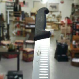 """Brisketkniv 50cm Brisketkniv, skinkkniv och såklart även för kallrökt lax. Swiss Made av Victorinox - ett kvalitetsföretag som inte kräver närmre beskrivning. Detta är den längsta varianten - en 50cm lång kniv med ett medelstyvt blad och sylvass egg. Olivslipningen (urgröpningarna) i bladet minskar risken för att det som du skär upp fastnar på bladet. Det bredare (högre) bladet är det som i första hand skiljer en Brisketkniv och Skinkkniv från en Laxkniv. Det bredare bladet gör det enklare att skära jämntjocka skivor. Med tanke på hur gelatinfylld en """"välbarkad"""" Brisket kan bli är det en grym fördel att använda en kniv likt denna. Du kan skära utan att riva sönder barken eller pressa ut gelatin från köttet. Det långa bladet gör att du kan skära skivor av även de allra största köttbitarna utan att ta omtag. Brisket har en tendens att av vara stora, inte minst US Beef av Black Angus. Även när du trancherar Julskinka så är det en klar fördel med en så här pass vass och lång kniv."""