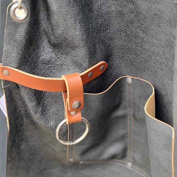 Förkläde - premium i mjukaste läder - Svart - Brickwalls and Barricades- X-cross remmar Ett förkläde av det mjukaste och mest följsamma läder som du kan fantisera om. Kryssremmar över ryggen som inte bara är snyggt, utan även mycket avlastande- ett hantverk från Holland. Ett skinnförkläde som bara blir snyggare och snyggare med tiden. Förklädet passar i sin stil, kvalitet och komfort inte bara både Foodies & Grillers utan även Frisörer, Barberare, Baristas och Restaurangpersonal. Färgen är Svart med naturliga variationer som skapar liv och naturligt mönster. Detta förkläde har ljusa läderremmar och silvrig metall som kontrastfärger. Skinnet är följsamt och mjukt från dag 1 och BBQmonster vågar lova att du knappast kommer att hitta ett skönare förkläde. Rejält tilltagna mått på remmarna för att detta snygga och praktiska förkläde passar alla, oavsett matchvikt. På förklädet finns ett par rejäla fickor samt en hållare för handduk (kocksläng) samt en ring med karbinhake för verktyg (saxar etc.) Längd på skinnet: 85 cm Bredd på skinnet: 57 cm