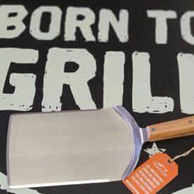 """Grillspade Traeger - Stor och tung XXL Spatula för Grill och Stekbord, även för smash-burger Detta är en grillspade, även kallat Spatula, av en sällan skådad kvalitet! Med en vikt på närmare kilot så är det enkelt att förstå att vi pratar om rejäla doningar och ingen """"spackel-spade"""". Helt klart ett alternativ som smash-burger-tool! Den användbara ytan är drygt 15cm bred och över 20 cm lång. Kanterna har en fasad och slipad kant vilket gör att du enkelt kan lägga an kanten hela vägen ned mot stekbordet. Denna spade som är gjord i rostfritt stål uppfyller ovanstående och har dessutom ett bekvämt och tjockt grepp av trä. På skaftet finns en upphängningsögla i metall. Godset är så pass grovt att du även kan smasha dina burgare om så önskas."""