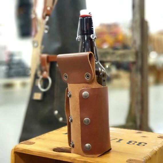 Flaskhölster för Förklädet Brunt flaskhölster i äkta skinn - ett hantverk från Holland. Ett brunt hölster där ölflaskor i olika storlek passar, detta tack vare justerbart genom knäppfäste. Ölflaskan hänger förvånansvärt stabilt på förklädet och du riskerar inte längre att ställa bort din öl. Flaskhölstret hängt i remmen som finns på 99% av alla förkläden, remmen som annars är tänkt för kockslängen (handduken). Flaskhölster för förkläde är en klockren present till den som redan har ett förkläde och givetvis perfekt produkt att addera ifall du tänker köpa något av BBQmonsters skinnförkläden. Färgen är brun (finns även i svart)