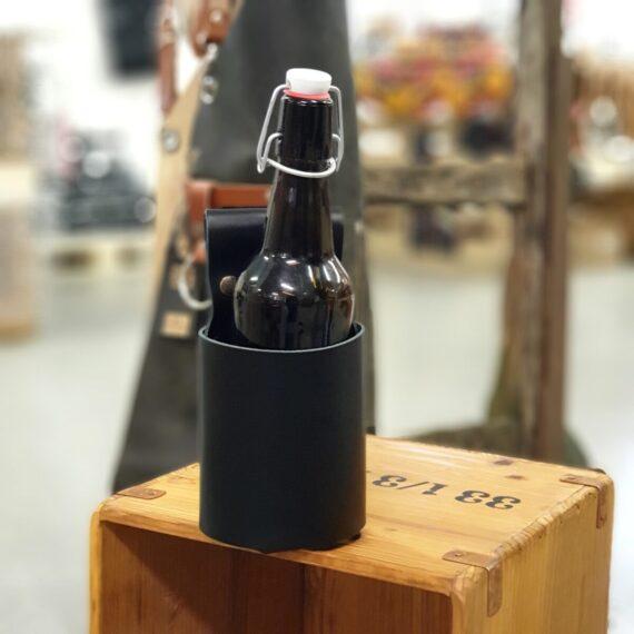 Flaskhölster för Förklädet Svart flaskhölster i äkta skinn - ett hantverk från Holland. Ett svart hölster där ölflaskor i olika storlek passar, detta tack vare justerbart genom knäppfäste. Ölflaskan hänger förvånansvärt stabilt på förklädet och du riskerar inte längre att ställa bort din öl. Flaskhölstret hängt i remmen som finns på 99% av alla förkläden, remmen som annars är tänkt för kockslängen (handduken). Flaskhölster för förkläde är en klockren present till den som redan har ett förkläde och givetvis perfekt produkt att addera ifall du tänker köpa något av BBQmonsters skinnförkläden.