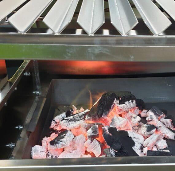 """Stor Santa Maria style grill Den coolaste grillen på den här sidan Sydamerika är förmodligen denna Santa Maria grill med hiss för det två sektioner stora V-gallret! Passa på: grillen finns till introduktionspriset 12999 kr! (Ordinariepriset 19999kr) Sluten grillning i täta kamados och smokers har helt klart sin plats men vi är fler och fler som vill köra GRILLNING. Det är ibland lätt att glömma bort vad ordet står för men grillning syftar på tillagning av mat över het eller mycket het värme, företrädesvis genom förbränning av träkol och torrt trä i kombination. För att lyckas med det behöver man ett starkt flöde av syretillförsel, något som man får med öppna grillar. Hiss Ett vanligt problem vid grillning kan vara att lågorna vill äta upp köttet eller fisken som ligger på gallret. Detta problem löser du med en Santa Maria style grill. Denna är nämligen utrustad med en hiss, vilken med gör att du kan variera höjden från glöden med över en halv meter! Du justerar höjden på några få sekunder genom att snurra det stora hjulet som via en vajer lyfter gallret upp eller ned. V-galler / V-grates Som om inte hissen vore nog så är denna stora Santa Maria style grill utrustad med så kallade V-galler eller V-grates. Dessa V-galler är byggda i mycket robust stål och har en stagning i form av ett 8mm tjockt kryss under, detta för att undvika att gallret skall böja sig vid de hetaste grillningarna. V-gallerna förhindrar att fett rinner rakt ned på glöden och skapar en fettbrand. Istället rinner fettet i botten på """"v:et"""" och eftersom att lutning är svagt framåt och att denna del av gallret avslutas med en hängränna så samlas fettet där. Där finns en hängränna på varje V-galler och dessa är avtagbara utan verktyg - detta för att underlätta rengöringen. Hylla Under grillen finns en underhylla i rostfritt stål där du kan förvara din grillprylar. Handgjord Grillen är gjord för hand och inte tillverkad i en större serie. Material är rostfritt (icke magnetiskt material vilket talar för a"""