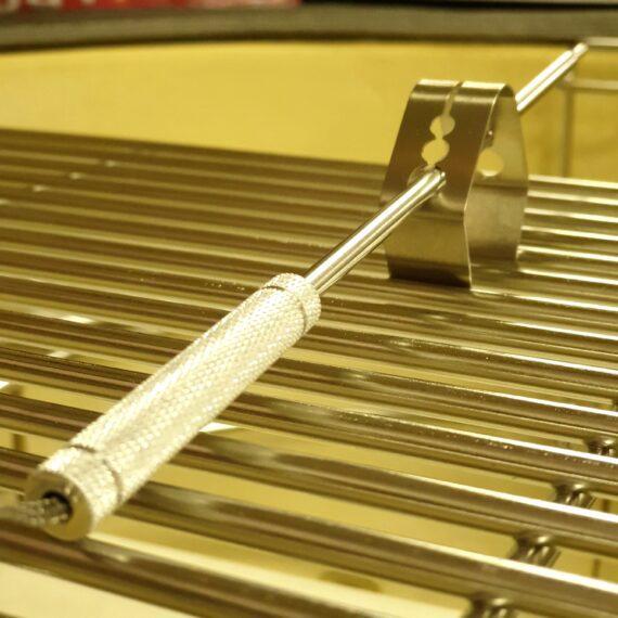"""Hållare för termometer-probe Nobelpris? Kanske inte riktigt men jäkligt bra uppfinning som gör att du kan sluta halvera potatisar för att hålla nålen i luften. En hållare i form av en klämma som kläms fast på gallret för att på så vis hålla termometer-proben i luften - ovanför gallret. Tre olika storlekar på hålen gör att denna hållare passar för alla typer av termometer-prober. Ta för vana att alltid använd denna hållare för den nål som du skall använda för att mäta temperaturen i själva grillen/kamadon. Detta ökar livslängden på nålen genom att skydda kabel och nål (probe) från den kraftiga överföringsvärme som ledningsförmågan i metall innebär (jämför med att hålla din hand inne i 170 graders värme mot att greppa ett objekt som är 170 grader varmt...detta är """"the power of ledningsförmåga""""...all metall leder bättre än luft)."""