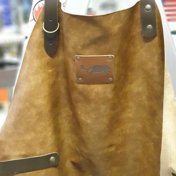 """Förkläde Ranch i äkta Skinn, Ranch = Ljusbrunt Pulled Pork edition är BBQmonster egna design som visar den """"springande grisen"""" jagad av pulled pork klor. Färgen på detta förkläde är Ranch, en ljusbrun (med drag åt det mörkbruna), ett förkläde i äkta skinn - ett hantverk från Holland. Förklädet är mjukt och smidigt redan från dag ett! Ingen prasslig eller hård """"inmjukningstid"""" krävs - bara häng på det och det hänger snyggt! Ett grill-förkläde som passar både i köket och vid grillen. Färgen är Ranch (ljusbrunt) och remmar och detaljer är mörka - allt i 100% äkta skinn. Skinnet är behandlat för att vara mer tåligt mot fläckar vilket minimerar behovet av under håll - bara torka av med fuktig trasa. Rejält tilltagna mått på remmarna för att detta snygga och praktiska förkläde passar alla, oavsett matchvikt. På förklädet finns en hållare för handduk (kocksläng) eller hölster för ölen! Längd på skinnet: 89 cm"""