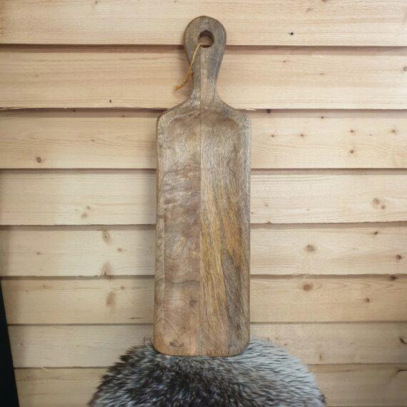 """Skärbräda 54cm x15 mangoträ - vintage shabby av mangoträ Denna skärbräda / charkbricka av trä (mangoträ) blir ett blickfång och praktiskt tillbehör i köket, väldigt instagramvänlig look. Varje skärbräda / bricka är unik och har gjorts för att se ut som att den har serverat många """"goa"""" saker genom åren. Denna skärbräda är lätt skålad vilket gör att ex salami och korv ligger väldigt bra på den. Skärbrädan / brickan av mangoträ är både praktisk och snygg och passar utmärkt på både julbordet, midsommarafton och kräftskivan. Använd den som en skärbräda och serveringsbricka för vin, ost, ölkorv, salami, frukt och annat småplock. Måtten på denna skärbräda / charkbricka är: Längd: 54cm Bredd: 15cm Tjocklek: 2,5cm"""