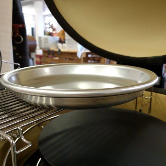 """Droppskål (30cm) i grov aluminium Denna droppskål i aluminium är gjord i Frankrike och är av absolut högsta kvalitet och givetvis livsmedelsgodkänd. I en Kamado Joe Classic med """"Slow roller"""" så passar detta fat helt perfekt med sin diameter på 30cm. Fördelen med aluminium av detta slag jämfört med andra material är att det inte slår sig och blir skevt samt att metallen inte ackumulerar värmen utan släpper den succesivt - detta gör att vätska som placeras i fatet inte avdunstar lika snabbt som vid användning av exempelvis en gjutjärnsskål. Slow rollern är inte helt enkel att hålla ren men med denna droppskål i grov aluminium placerad ovanpå så kan du fånga upp merparten av dropparna utan att du förstör den """"rörelse"""" som slow rollern skapar (läs: om skålen skulle vara 40 cm i diameter skulle röken som produceras gå ut vid sidorna av gallret istället för att rulla upp för en direktträff). Du kan använda den """"torr"""" (klä då gärna den med alufolie för enkel rengöring) eller fylld med vatten - rymmer några liter vatten. När du fyller den med vatten eller isbad kommer du påtagligt sänka temperaturen i din Kamado - perfekt om du vill lägga dig en bra bit under 100 grader och röka köttet eller fisken under längre tid. Just när man röker laxsidor och vill utöka tiden i röken så är denna teknik mycket användbar. Använd den under de feta köttbitarna när du kör low & Slow utan övervakning, detta för att fånga upp fett och förhindra en fettbrand. En droppskål eller droppanna kan även användas för att tillföra fukt för en mer optimal rökmiljö - så länge köttet är fuktigt på utsidan fortsätter rökpartiklar att fastna, när utsidan är torr upphör rökupptaget på grund av rökpartiklarnas oförmåga att fästa. Ett annat användningsområde för denna skål är för servering av exempelvis skaldjur eller kött. Diameter 30cm (toppen) 23 cm (basen), höjd 4 cm droppskål eller serveringsfat förhindrar fettbrand tålig och robust (nästan 4 hekto ren alu) kyleffekt genom ett par liters volym OBS - bör d"""