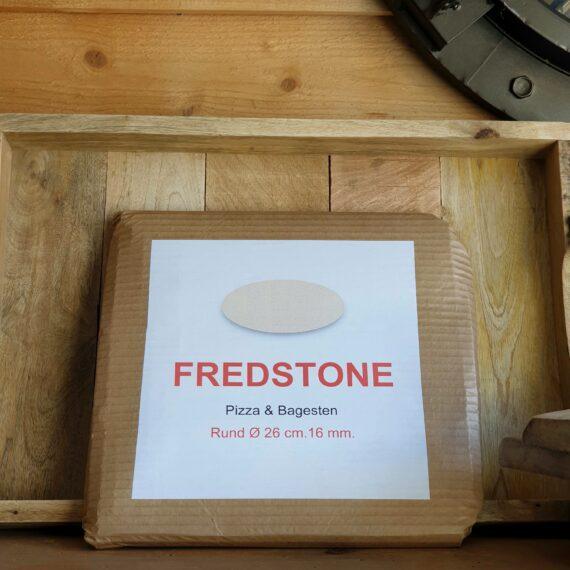 """Pizzasten - Fredstone 26cm perfekt för Kamado Joe junior mfl Fredstone för bordsgrillar och bordskamados 26cm i diameter Detta är pizzastenen som har revolutionerat världen. Hetta upp den så mycket du kan och ändå är det omöjligt att bränna pizzan. En uppfinning av en dansk bagare som fått till ett material som innehåller mycket luft och detta gör inte bara stenen lättare - den blir precis lagom """"isolerande"""" (istället för att bara bli varmare och varmare så släpper den värme efter hand och är därmed alltid helt rätt i temp). Pizza på pizzasten är hemligheten till en """"köp-pizza-känsla"""" där degen är krispig och genombakad utan att blivit som ett knäckebröd. Passar både i grill och ugn. Många är vi som på början av 2000 talet letade efter det perfekta receptet på pizzadeg i tron att detta var skillnaden som gjorde skillnaden - vi hade FEL. Hemligheten till en bra bakad pizza ligger istället i att degen bakas under ifrån, från ett redan hett underlag - alltså en upphettad pizzasten. Lagom temperatur i grillen (eller ugnen) är 250 till 300 grader. För många är det då grillen som gäller, då de flesta hushållsugnar stannar på runt 225grader. Tekniken är: varm upp stenen, kavla ut degen på ett bakplåtspapper, dressa din pizza med dina favoriter men börja alltid med tomatsåsen, därefter pizzaosten, sen är det valfritt. Lyft över pizzan på sitt papper, låt den landa på stenen och ganska snart kan du rycka bort pappret. Använd pizzaspade (artikel nr 31016) för att lyfta bort pizzan när osten bubblar. Diameter 26 cm"""