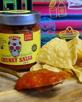 Chunky salsa - ananas chipotle - perfekt till tortillas och tacos - Ekologisk Skånsk Chili Chunky salsa med rötterna i Skånska myllan, närmare bestämt i världsmetropolen Asmundtorp, känn på den världen! Denna Chunky salsa med smak av ananas och chipotle görs på deras egenodlade och obesprutade chilis, även koriandern är egenodlad. Tomaterna kommer från Skåne. Produktionen sker utan konserveringsmedel men tack vare en värmebehandling är hållbarheten mycket god. Chunky salsa ananas chipotle är djupröd till färgen och ger ett tydligt fruktigt svar när den landar på tungan. Chilistinget är relativt svagt men fylls ut av en naturlig rökighet från chipotle (rökt poblano chili). Koriander, lime. äpple och en lätt sälta kompletterar den fina sötman som kommer från ananas - och därmed har vi en välsmakande chunky salsa som inte lämnar någon smaklök oberörd. Använd denna Chunky salsa ananas chipotle som dip till tortillachips eller sleva ut den över dina tacos - go loco! 225 ml