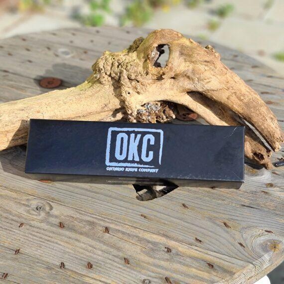 """JaktKniv edt. - Old Hickory - ruggigt vasst 5,5"""" blad i kolstål inkl Läderslida En perfekt present till den jägaren och BBQ-entusiasten! 5,5"""" Jaktkniv med läderslida som definitivt gör sig både på jakten, i förklädet på BBQ-tävlingen och på instagram-bilden. Detta är jakt edt. av den älskade serien av kolstålsknivar från OKC - Ontario Knife Company som är kända för sina fina kolstålsknivar och inte minst sina """"butcher knifes"""". Denna rejäla och rustika kniv har en rejäl grovlek på knivens rygg vilket tillåter att du kan ta i riktigt mycket utan att böja kniven. Det relativt korta bladet är uppskattat då det gör kniven lätt att styra. Bredden på spetsen gör att många väljer att använda kniven för att vända både burgare och köttbitar eller för att peta runt i kolen. Slidan är gjord av tjockt och fint läder och klarar skärp upp till en bredd på 6cm. Kolstål går att få rakbladsvasst utan specialinstrument. Man skall dock vara medveten att med fördelar kommer nackdelar. Mjukt stål tappar skärpan lättare än hårt stål och rostar lättare - de flesta tycker dock att fördelarna överväger nackdelarna och så länge du torkar av kniven efter varje användning kan du förvänta dig en kniv som bara blir snyggare med åren med den patina som bildas. OKC - Ontario Knife Company är precis som namnet antyder ett Amerikanskt företag. Företaget har tillverkat knivar sedan 1889 och serien """"Old Hickory"""" kom till redan 1923 och har sedan dess sett ut som nu - en klassiker med andra ord. Tillverkningen sker fortfarande i USA och det är riktigt imponerande knivar som bankas ut. Längd på bladet: 14 cm . Längd på skaftet: 11 cm: Plast för ett rejält grepp även om du har större händer än snitt-Svensson, något som påverkar säkerheten."""