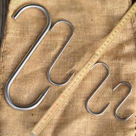 Köttkrokar / slaktkrokar Från 80mm till 250mm Rostfritt tyskt kvalitetsstål Köttkrokar / Slaktkrokar av proffsmodell, gjorda i Tyskland i rostfritt stål. Dessa köttkrokar / Slaktkrokar kan du använda för mycket mer än att hänga upp ditt villebråd; spänn en tråd genom din rök eller grill och häng upp ett köttstycke för rökning, rök ett par korvar eller firrar hängandes istället för på galler som då leder värmen snabbare in köttet - på så vis skapar du mer tid i rök innan måltemp uppnås. Om du gillar att inreda ditt hem och inte minst ditt kök på ett lantligt och rustikt vis så kan du köpa en lättare kätting som du fäster på två punkter i taket, i denna fäster du någon form av stav (allt från kvastskaft till en rustik gardinstång) varefter du hänger upp Köttkrokar / slaktkrokar. Här kan du sen hänga de redskap som du använder mest, alltifrån stekpannor till köttyxor och saxar. Finns i följande storlekar: Small: 80mm lång, gapar 30mm, 4mm grov, 16 gram Medium: 120mm lång, gapar 38mm, 5mm grov, 32 gram Large: 160mm lång, gapar 45mm, 6mm grov, 60 gram XXL: 250mm lång, gapar 68mm, 10mm grov, 375 gram tung(!)