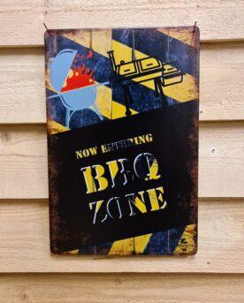 """Tavla skylt """"BBQ Zone"""" Vintage skyltar i plåt. Skylt för kök, utekök, grillhörna, BBQ, Bar, Mancave Dekorera din favoritplats med skyltar och metalltavlor i rustik vintage design som bjuder in till ett skratt eller två ;) Now Entering BBQ ZONE är en plåtskylt som talar sitt tydliga språk - här bor kvarterets grillkung och seriös grillare! Tavlor i metall och plåtskyltar? BBQmonster har en häftig samling tavlor och skyltar i metall som kan vara den perfekta presenten eller tillbehöret till presenten som gör pricken över i:et, eller """"the prick over the eye"""" som man säger i Amerikat... Metalltavlor för grill och BBQ är efterfrågade dekorer till utekök, mancaves och grillhörnor och med BBQmonsters uppsättning är chansen god att du hittar en skylt som passar just dig eller den person du skall köpa presenten till. Ett presenttips kan vara att om du köper låt säga ett paket spanska ginglas att då komplettera med en skylt som förstärker budskapet. Samma sak kan appliceras Ölglas, Kamados osv. Livsnjutare, Foodies och grillare är ofta glada för både god mat och god dryck. Därför kretsar många av dessa vintage skyltar och metalltavlor på tema Mat, såsom recepttavlor (för exempelvis Pulled pork, Revben / Ribs och Brisket). Eller Dryck (whisky, bourbon, beer, öl, IPA, Cider, Stout och inte minst modedrycken GIN). Tavlorna i metall finns i ett antal olika format, men där det vanligaste är måtten 20 x 30 (stående) cm eller 30 x 20 (liggande). Det finns även ett par större modeller (bland annat runda). Skyltarna har en vikt kant så inga vassa kanter existerar. Hörnen är försedda med hål (på det fyrkantiga tavlorna) där du enkelt med två eller fyra spik eller skruvar fäster upp tavlan på underlaget. Du kan även använda dubbelhäftande tejp om det passar bättre mot underlaget. Du hittar alla tavlor och skyltar under kategorin Tavlor metall (www.bbqmonster.se/produkt-kategori/tavlor/)"""