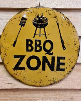 """Tavla skylt """"BBQ Zone"""" Vintage skyltar i plåt. Skylt för kök, utekök, grillhörna Dekorera din favoritplats med skyltar och metalltavlor i rustik vintage design som bjuder in till ett skratt eller två ;) Rund plåtskylt med texten """"BBQ Zone"""". Snygg skylt som pekar ut grillplatsen och grillhörnan på ett tydligt sätt. Denna skylt är """"embossed"""" alltså präglad, utbankad med förhöjningar som ger ett snyggt djup i bilden. Tavlor i metall och plåtskyltar? BBQmonster har en häftig samling tavlor och skyltar i metall som kan vara den perfekta presenten eller tillbehöret till presenten som gör pricken över i:et, eller """"the prick over the eye"""" som man säger i Amerikat... Metalltavlor för grill och BBQ är efterfrågade dekorer till utekök, mancaves och grillhörnor och med BBQmonsters uppsättning är chansen god att du hittar en skylt som passar just dig eller den person du skall köpa presenten till. Ett presenttips kan vara att om du köper låt säga ett paket spanska ginglas att då komplettera med en skylt som förstärker budskapet. Samma sak kan appliceras Ölglas, Kamados osv. Livsnjutare, Foodies och grillare är ofta glada för både god mat och god dryck. Därför kretsar många av dessa vintage skyltar och metalltavlor på tema Mat, såsom recepttavlor (för exempelvis Pulled pork, Revben / Ribs och Brisket). Eller Dryck (whisky, bourbon, beer, öl, IPA, Cider, Stout och inte minst modedrycken GIN). Tavlan hänger du enkelt upp på en spik eller skruv, i snöret som medföljer. Du kan även använda dubbelhäftande tejp om det passar bättre mot underlaget. BBQ zone - en plåtskylt, rund modell 30cm i diameter, med text och bild präglat ur plåten. Du hittar alla tavlor och skyltar under kategorin Tavlor metall (www.bbqmonster.se/produkt-kategori/tavlor/)"""