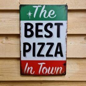 """Tavla skylt """"Best Pizza in Town"""" Vintage skyltar i plåt. Skylt för kök, utekök, grillhörna, BBQ, Bar, Mancave Dekorera din favoritplats med skyltar och metalltavlor i rustik vintage design som bjuder in till ett skratt eller två ;) Är du fast i Pizza-träsket med leopardmönstrade degkanter och degrecept som jäser längre än en sättning egenbryggd öl? Då är det kanske så att du eller objektet för denna skylt är värd en skylt som berättar vad det hela handlar om: The Best Pizza in Town Tavlor i metall och plåtskyltar? BBQmonster har en häftig samling tavlor och skyltar i metall som kan vara den perfekta presenten eller tillbehöret till presenten som gör pricken över i:et, eller """"the prick over the eye"""" som man säger i Amerikat... Metalltavlor för grill och BBQ är efterfrågade dekorer till utekök, mancaves och grillhörnor och med BBQmonsters uppsättning är chansen god att du hittar en skylt som passar just dig eller den person du skall köpa presenten till. Ett presenttips kan vara att om du köper låt säga ett paket spanska ginglas att då komplettera med en skylt som förstärker budskapet. Samma sak kan appliceras Ölglas, Kamados osv. Livsnjutare, Foodies och grillare är ofta glada för både god mat och god dryck. Därför kretsar många av dessa vintage skyltar och metalltavlor på tema Mat, såsom recepttavlor (för exempelvis Pulled pork, Revben / Ribs och Brisket). Eller Dryck (whisky, bourbon, beer, öl, IPA, Cider, Stout och inte minst modedrycken GIN). Tavlorna i metall finns i ett antal olika format, men där det vanligaste är måtten 20 x 30 (stående) cm eller 30 x 20 (liggande). Det finns även ett par större modeller (bland annat runda). Skyltarna har en vikt kant så inga vassa kanter existerar. Hörnen är försedda med hål (på det fyrkantiga tavlorna) där du enkelt med två eller fyra spik eller skruvar fäster upp tavlan på underlaget. Du kan även använda dubbelhäftande tejp om det passar bättre mot underlaget. Du hittar alla tavlor och skyltar under kategorin Tavlor metall """