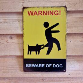 """Tavla skylt """"Beware of the dog"""" Vintage skyltar i plåt. Skylt för kök, utekök, grillhörna, BBQ, Bar, Mancave Dekorera din favoritplats med skyltar och metalltavlor i rustik vintage design som bjuder in till ett skratt eller två ;) Få saker kan få en potentiell inbrottstjuv att tänka till en extra gång så bra som en skylt som varnar för en argsint hund som äter upp vaderna på eventuella trespassers...Skydda din grillhörna och din värdefulla grillprylar och kamados med en HUND - varning för hunden, Beware of the dog! Tavlor i metall och plåtskyltar? BBQmonster har en häftig samling tavlor och skyltar i metall som kan vara den perfekta presenten eller tillbehöret till presenten som gör pricken över i:et, eller """"the prick over the eye"""" som man säger i Amerikat... Metalltavlor för grill och BBQ är efterfrågade dekorer till utekök, mancaves och grillhörnor och med BBQmonsters uppsättning är chansen god att du hittar en skylt som passar just dig eller den person du skall köpa presenten till. Ett presenttips kan vara att om du köper låt säga ett paket spanska ginglas att då komplettera med en skylt som förstärker budskapet. Samma sak kan appliceras Ölglas, Kamados osv. Livsnjutare, Foodies och grillare är ofta glada för både god mat och god dryck. Därför kretsar många av dessa vintage skyltar och metalltavlor på tema Mat, såsom recepttavlor (för exempelvis Pulled pork, Revben / Ribs och Brisket). Eller Dryck (whisky, bourbon, beer, öl, IPA, Cider, Stout och inte minst modedrycken GIN). Tavlorna i metall finns i ett antal olika format, men där det vanligaste är måtten 20 x 30 (stående) cm eller 30 x 20 (liggande). Det finns även ett par större modeller (bland annat runda). Skyltarna har en vikt kant så inga vassa kanter existerar. Hörnen är försedda med hål (på det fyrkantiga tavlorna) där du enkelt med två eller fyra spik eller skruvar fäster upp tavlan på underlaget. Du kan även använda dubbelhäftande tejp om det passar bättre mot underlaget. Du hittar alla tavlor och skyl"""