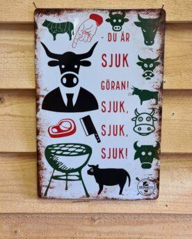"""Tavla skylt """"Kannibal-tjuren Göran"""" Vintage skyltar i plåt. Skylt för kök, utekök, grillhörna, BBQ, Bar, Mancave Dekorera din favoritplats med skyltar och metalltavlor i rustik vintage design som bjuder in till ett skratt eller två ;) Här har vi minnesbild från den klassiska humortidning Larsson, där förskräckta kossor står intryckta i ett bås. Med darriga klövar pekar alla på """"Göran"""" som i ett hörn av stallet står och vänder T-bone-steaks på en klotgrill...en Kannibal-tjur... Visst det är sjuk och morbid humor men jävlar vad intelligent. Tavlor i metall och plåtskyltar? BBQmonster har en häftig samling tavlor och skyltar i metall som kan vara den perfekta presenten eller tillbehöret till presenten som gör pricken över i:et, eller """"the prick over the eye"""" som man säger i Amerikat... Metalltavlor för grill och BBQ är efterfrågade dekorer till utekök, mancaves och grillhörnor och med BBQmonsters uppsättning är chansen god att du hittar en skylt som passar just dig eller den person du skall köpa presenten till. Ett presenttips kan vara att om du köper låt säga ett paket spanska ginglas att då komplettera med en skylt som förstärker budskapet. Samma sak kan appliceras Ölglas, Kamados osv. Livsnjutare, Foodies och grillare är ofta glada för både god mat och god dryck. Därför kretsar många av dessa vintage skyltar och metalltavlor på tema Mat, såsom recepttavlor (för exempelvis Pulled pork, Revben / Ribs och Brisket). Eller Dryck (whisky, bourbon, beer, öl, IPA, Cider, Stout och inte minst modedrycken GIN). Tavlorna i metall finns i ett antal olika format, men där det vanligaste är måtten 20 x 30 (stående) cm eller 30 x 20 (liggande). Det finns även ett par större modeller (bland annat runda). Skyltarna har en vikt kant så inga vassa kanter existerar. Hörnen är försedda med hål (på det fyrkantiga tavlorna) där du enkelt med två eller fyra spik eller skruvar fäster upp tavlan på underlaget. Du kan även använda dubbelhäftande tejp om det passar bättre mot underlaget. ...kan"""