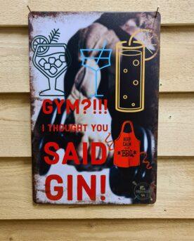 """Tavla """"Gym? Gin!"""" plåtskylt skylt vintage design i plåt vintage metall, metalltavla för kök, utekök, grillhörna, BBQ, Bar, Mancave Dekorera din favoritplats med metalltavlor i rustik vintage design som bjuder in till ett skratt eller två ;) GYM? I thought you said Gin! - ja det är lätt och gott att höra fel ibland! BBQmonster har en häftig samling tavlor i metall som kan vara den perfekta presenten eller tillbehöret till presenten som gör pricken över i:et, eller """"the prick over the eye"""" som man säger i Amerikat... Metalltavlor för grill och BBQ är efterfrågade dekorer till utekök, mancaves och grillhörnor och med BBQmonsters uppsättning är chansen god att du hittar något som passar just dig eller den person du skall köpa presenten till. Livsnjutare, Foodies och grillare är ofta glada för både god mat och god dryck. Därför kretsar många av dessa metalltavlor på tema Mat, såsom recepttavlor (för exempelvis Pulled pork, Revben / Ribs och Brisket). Eller Dryck (whisky, bourbon, beer, öl, IPA, Cider, Stout och inte minst modedrycken GIN). Tavlorna i metall finns i ett antal olika format, men där det vanligaste är måtten 20 x 30 (stående) cm eller 30 x 20 (liggande). Det finns även ett par större modeller (bland annat runda). Tavlorna har en vikt kant så inga vassa kanter existerar. Hörnen är försedda med hål (på det fyrkantiga tavlorna) där du enkelt med två eller fyra spik eller skruvar fäster upp tavlan på underlaget. Du kan även använda dubbelhäftande tejp om det passar bättre mot underlaget. Du hittar alla tavlor under kategorin Tavlor metall (www.bbqmonster.se/tavlor)"""