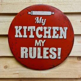 """Tavla skylt """"My kitchen, My rules"""" Vintage skyltar i plåt. Skylt för kök, utekök, grillhörna Dekorera din favoritplats med skyltar och metalltavlor i rustik vintage design som bjuder in till ett skratt eller två ;) Rund plåtskylt med texten """"My kitchen, my rules"""". Snygg skylt som fördelar brödkaveln till ägaren av köket (extra rätt om ägarinnan råkar heta My...) - rättvisan när den är som bäst. Denna skylt är """"embossed"""" alltså präglad, utbankad med förhöjningar som ger ett snyggt djup i bilden. Tavlor i metall och plåtskyltar? BBQmonster har en häftig samling tavlor och skyltar i metall som kan vara den perfekta presenten eller tillbehöret till presenten som gör pricken över i:et, eller """"the prick over the eye"""" som man säger i Amerikat... Metalltavlor för grill och BBQ är efterfrågade dekorer till utekök, mancaves och grillhörnor och med BBQmonsters uppsättning är chansen god att du hittar en skylt som passar just dig eller den person du skall köpa presenten till. Ett presenttips kan vara att om du köper låt säga ett paket spanska ginglas att då komplettera med en skylt som förstärker budskapet. Samma sak kan appliceras Ölglas, Kamados osv. Livsnjutare, Foodies och grillare är ofta glada för både god mat och god dryck. Därför kretsar många av dessa vintage skyltar och metalltavlor på tema Mat, såsom recepttavlor (för exempelvis Pulled pork, Revben / Ribs och Brisket). Eller Dryck (whisky, bourbon, beer, öl, IPA, Cider, Stout och inte minst modedrycken GIN). Tavlan hänger du enkelt upp på en spik eller skruv, i snöret som medföljer. Du kan även använda dubbelhäftande tejp om det passar bättre mot underlaget. My kitchen, my rules - en plåtskylt, rund modell 30cm i diameter, med text och bild präglat ur plåten. Du hittar alla tavlor och skyltar under kategorin Tavlor metall (www.bbqmonster.se/produkt-kategori/tavlor/) Tavla till hemmakocken"""
