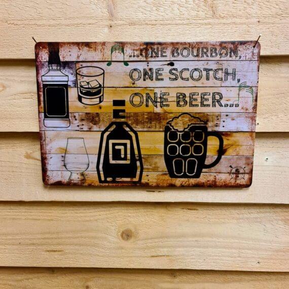 """Tavla """"One bourbon"""" plåtskylt skylt i vintage designvintage metall, metalltavla för kök, utekök, grillhörna, BBQ, Bar, Mancave Dekorera din favoritplats med metalltavlor i rustik vintage design som bjuder in till ett skratt eller två ;) ...one bourbon...one scotch...one beer - citat hämtat från en riktig rockklassiker! (lyssna gärna på låten på Spotify, versionen med George Thorogood & the Destroyers - den är grym!) BBQmonster har en häftig samling tavlor i metall som kan vara den perfekta presenten eller tillbehöret till presenten som gör pricken över i:et, eller """"the prick over the eye"""" som man säger i Amerikat... Metalltavlor för grill och BBQ är efterfrågade dekorer till utekök, mancaves och grillhörnor och med BBQmonsters uppsättning är chansen god att du hittar något som passar just dig eller den person du skall köpa presenten till. Livsnjutare, Foodies och grillare är ofta glada för både god mat och god dryck. Därför kretsar många av dessa metalltavlor på tema Mat, såsom recepttavlor (för exempelvis Pulled pork, Revben / Ribs och Brisket). Eller Dryck (whisky, bourbon, beer, öl, IPA, Cider, Stout och inte minst modedrycken GIN). Tavlorna i metall finns i ett antal olika format, men där det vanligaste är måtten 20 x 30 (stående) cm eller 30 x 20 (liggande). Det finns även ett par större modeller (bland annat runda). Tavlorna har en vikt kant så inga vassa kanter existerar. Hörnen är försedda med hål (på det fyrkantiga tavlorna) där du enkelt med två eller fyra spik eller skruvar fäster upp tavlan på underlaget. Du kan även använda dubbelhäftande tejp om det passar bättre mot underlaget. Du hittar alla tavlor under kategorin Tavlor metall (www.bbqmonster.se/tavlor)"""