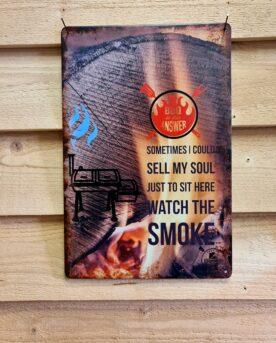 """Tavla skylt """"...sell my soul"""" Vintage skyltar i plåt. Skylt för kök, utekök, grillhörna, BBQ, Bar, Mancave Dekorera din favoritplats med skyltar och metalltavlor i rustik vintage design som bjuder in till ett skratt eller två ;) Visst är det ren och skär avslappning och på gränsen till hypnos att betrakta röken leta sig ut grillen, smokern eller kamadon. Att sitta där en kylig dag och känna doften och se röken skapa figurer som letar sig mot himmeln är en upplevelse värd att ta vara på - ...sometimes I could sell my soul just to sit here watch the smoke. Tavlor i metall och plåtskyltar? BBQmonster har en häftig samling tavlor och skyltar i metall som kan vara den perfekta presenten eller tillbehöret till presenten som gör pricken över i:et, eller """"the prick over the eye"""" som man säger i Amerikat... Metalltavlor för grill och BBQ är efterfrågade dekorer till utekök, mancaves och grillhörnor och med BBQmonsters uppsättning är chansen god att du hittar en skylt som passar just dig eller den person du skall köpa presenten till. Ett presenttips kan vara att om du köper låt säga ett paket spanska ginglas att då komplettera med en skylt som förstärker budskapet. Samma sak kan appliceras Ölglas, Kamados osv. Livsnjutare, Foodies och grillare är ofta glada för både god mat och god dryck. Därför kretsar många av dessa vintage skyltar och metalltavlor på tema Mat, såsom recepttavlor (för exempelvis Pulled pork, Revben / Ribs och Brisket). Eller Dryck (whisky, bourbon, beer, öl, IPA, Cider, Stout och inte minst modedrycken GIN). Tavlorna i metall finns i ett antal olika format, men där det vanligaste är måtten 20 x 30 (stående) cm eller 30 x 20 (liggande). Det finns även ett par större modeller (bland annat runda). Skyltarna har en vikt kant så inga vassa kanter existerar. Hörnen är försedda med hål (på det fyrkantiga tavlorna) där du enkelt med två eller fyra spik eller skruvar fäster upp tavlan på underlaget. Du kan även använda dubbelhäftande tejp om det passar bättre mot un"""