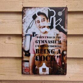 """Tavla skylt """"in the gymnasium..."""" Vintage skyltar i plåt. Skylt för kök, utekök, grillhörna, BBQ, Bar, Mancave Dekorera din favoritplats med skyltar och metalltavlor i rustik vintage design som bjuder in till ett skratt eller två ;) En plåtskylt / kökstavla som har sina rötter i ett citat hört i en Svensk feelgood film, när killen som förmodligen sov sig igenom engelska lektionerna, vid ett samtal om matlagning skall berätta lite om sin bakgrund: """"...when I was in the gymnasium I was considering being a cock"""" . Skylten kan passa fint in hos oss alla hobbykockar / hemmakockar utan skolning men med ett brinnande intresse för god mat, god dryck och livets goda. - smile, if you can! ;) Tavlor i metall och plåtskyltar? BBQmonster har en häftig samling tavlor och skyltar i metall som kan vara den perfekta presenten eller tillbehöret till presenten som gör pricken över i:et, eller """"the prick over the eye"""" som man säger i Amerikat... Metalltavlor för grill och BBQ är efterfrågade dekorer till utekök, mancaves och grillhörnor och med BBQmonsters uppsättning är chansen god att du hittar en skylt som passar just dig eller den person du skall köpa presenten till. Ett presenttips kan vara att om du köper låt säga ett paket spanska ginglas att då komplettera med en skylt som förstärker budskapet. Samma sak kan appliceras Ölglas, Kamados osv. Livsnjutare, Foodies och grillare är ofta glada för både god mat och god dryck. Därför kretsar många av dessa vintage skyltar och metalltavlor på tema Mat, såsom recepttavlor (för exempelvis Pulled pork, Revben / Ribs och Brisket). Eller Dryck (whisky, bourbon, beer, öl, IPA, Cider, Stout och inte minst modedrycken GIN). Tavlorna i metall finns i ett antal olika format, men där det vanligaste är måtten 20 x 30 (stående) cm eller 30 x 20 (liggande). Det finns även ett par större modeller (bland annat runda). Skyltarna har en vikt kant så inga vassa kanter existerar. Hörnen är försedda med hål (på det fyrkantiga tavlorna) där du enkelt med två """