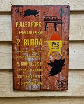 """Tavla skylt """"recept på Ribs"""" Vintage skyltar i plåt. Skylt för kök, utekök, grillhörna, BBQ, Bar, Mancave Dekorera din favoritplats med skyltar och metalltavlor i rustik vintage design som bjuder in till ett skratt eller två ;) Här är skylten och tavlan i plåt som ger dig ett gott förslag på hur du tillagar Pulled Pork Receptet blir dekorativt i både köket och uteköket. Du vet väl att BBQmonsters butik i Ödåkra har iberico Karré i frysen varje dag! Tavlor i metall och plåtskyltar? BBQmonster har en häftig samling tavlor och skyltar i metall som kan vara den perfekta presenten eller tillbehöret till presenten som gör pricken över i:et, eller """"the prick over the eye"""" som man säger i Amerikat... Metalltavlor för grill och BBQ är efterfrågade dekorer till utekök, mancaves och grillhörnor och med BBQmonsters uppsättning är chansen god att du hittar en skylt som passar just dig eller den person du skall köpa presenten till. Ett presenttips kan vara att om du köper låt säga ett paket spanska ginglas att då komplettera med en skylt som förstärker budskapet. Samma sak kan appliceras Ölglas, Kamados osv. Livsnjutare, Foodies och grillare är ofta glada för både god mat och god dryck. Därför kretsar många av dessa vintage skyltar och metalltavlor på tema Mat, såsom recepttavlor (för exempelvis Pulled pork, Revben / Ribs och Brisket). Eller Dryck (whisky, bourbon, beer, öl, IPA, Cider, Stout och inte minst modedrycken GIN). Tavlorna i metall finns i ett antal olika format, men där det vanligaste är måtten 20 x 30 (stående) cm eller 30 x 20 (liggande). Det finns även ett par större modeller (bland annat runda). Skyltarna har en vikt kant så inga vassa kanter existerar. Hörnen är försedda med hål (på det fyrkantiga tavlorna) där du enkelt med två eller fyra spik eller skruvar fäster upp tavlan på underlaget. Du kan även använda dubbelhäftande tejp om det passar bättre mot underlaget. Recepttavla och recept på Ribs Du hittar alla tavlor och skyltar under kategorin Tavlor metall (ww"""