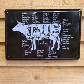 """Tavla skylt """"styckningsschema ko"""" Vintage skyltar i plåt. Skylt för kök, utekök, grillhörna, BBQ, Bar, Mancave Dekorera din favoritplats med skyltar och metalltavlor i rustik vintage design som bjuder in till ett skratt eller två ;) Styckningsschema och styckschema har länge varit en populär inredningsdetalj i köket. Nu finns även denna tavla / plåtskylt för GRIS, Pork, Pig, som är mer hållbar och bättre lämpad för uteköket och grillhörnan. Ett styckningsschema är även användbart för att bättre förstå de olika delarna och lära sig namnen på styckdelarna och var dessa rent schematiskt sitter på djuret. Denna skylt är """"embossed"""" alltså präglad, utbankad med förhöjningar som ger ett snyggt djup i bilden. Tavlor i metall och plåtskyltar? BBQmonster har en häftig samling tavlor och skyltar i metall som kan vara den perfekta presenten eller tillbehöret till presenten som gör pricken över i:et, eller """"the prick over the eye"""" som man säger i Amerikat... Metalltavlor för grill och BBQ är efterfrågade dekorer till utekök, mancaves och grillhörnor och med BBQmonsters uppsättning är chansen god att du hittar en skylt som passar just dig eller den person du skall köpa presenten till. Ett presenttips kan vara att om du köper låt säga ett paket spanska ginglas att då komplettera med en skylt som förstärker budskapet. Samma sak kan appliceras Ölglas, Kamados osv. Livsnjutare, Foodies och grillare är ofta glada för både god mat och god dryck. Därför kretsar många av dessa vintage skyltar och metalltavlor på tema Mat, såsom recepttavlor (för exempelvis Pulled pork, Revben / Ribs och Brisket). Eller Dryck (whisky, bourbon, beer, öl, IPA, Cider, Stout och inte minst modedrycken GIN). Tavlorna i metall finns i ett antal olika format, men där det vanligaste är måtten 20 x 30 (stående) cm eller 30 x 20 (liggande). Det finns även ett par större modeller (bland annat runda). Skyltarna har en vikt kant så inga vassa kanter existerar. Hörnen är försedda med hål (på det fyrkantiga tavlorna) dä"""