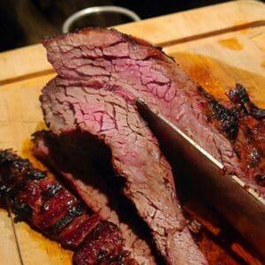 """Vad är Flap-Meat: Flap är INTE Flank. Flap är en platt köttbit, i tjocklek med en flankstek men oftast något längre. Biten är placerad i anslutning med flanken men det är en muskel som inte har jobbat lika statiskt som flanken (som är muskeln som håller in buken). Detta gör att köttet är mycket mindre stumt än flankstek, mer som ett dragspel. Mjukt kött, """"fluffigt"""" trots grova muskelfiber. Eftersom att det är en muskel som mest har """"hängt med"""" och inte belastats tungt så pratar vi om en muskel som i det närmsta saknar stödvävnad och brosk. Vilket innebär att low & slow inte krävs, snarare tvärt om - köttet skall """"bli klart"""" - ju snabbare och hetare desto bättre. Så här grillar du Flap: Gör grillen redo för riktigt het grillning. Rubba exempelvis med Black and white with a sting från #RubsByBBQmonster. Grilla hot & fast över het kol. Passa köttet noga, vänd när fettet börjar brinna eller när du ser att det svettas igenom. Lyft upp köttet från gallret och mät i c/c genom att dra en snabbtermometer sakta genom köttet. Våga köra det upp mot 70 grader i c/c och låt det få en hårt grillad yta. Köttet skärs lämpligen i 1 cm tjocka skivor. Var noga att skära tvärs över muskelfibrerna och inte längs med dessa. Formatet på köttbiten är oftast att likna vid Sverigekartan, så lägg köttet från """"Norr till söder"""" med Skåne närmst dig, skär sedan köttet från Norr till Söder, alltså långa skivor. Du skär nu AV dessa fibrer, ej längs med. Genom att lägga kniven på diagonalen får du lite större skivor. Tips: Är kolen lite lam? För att få upp värmen ytterligare kan du med fördel slänga på lite torrt rökträ, testa ek eller hickory. Detta ger mer direkt hetta än glödande kol och tillför dessutom nya smaker och nyanser."""
