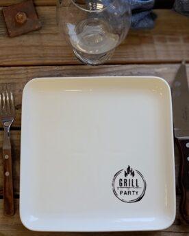 """Tallrik """"Grillparty"""" Keramik 23x23cm kvadratisk tallrik med låg kant Pris för 6pack Snygg GRILL-tallrik för grillfesten och uteköket Dessa glaserade, kvadratiska tallrikar ser allmänt fräscha ut i skrud av vitt, låga kanter och raka linjer. I nedre högra hörnet finns ett tryck som berättar vad det handlar om: Grillparty! (ganska praktiskt ifall någon helt skulle tappa det en blöt kväll;)) Tallrikarna som ingår är sex till antalet och grillparty tallrikarna tåler diskmaskin, inte en helt oviktig detalj klocka 02:45. MÅTT: 23X23CM Så passa på att duka snyggt i uteköket och säkra en fräsch BBQlifestyle som inte lämnar någon oberörd. Ute efter aluminium brickor och tallrikar? https://bbqmonster.se/produkt-kategori/aluminium-brickor-bbq/"""