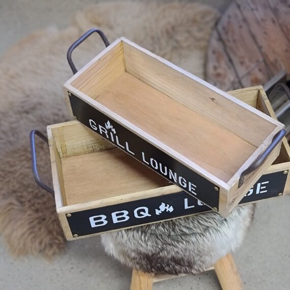 """Bricka / låda / back 2pack snygga trälådor handtag i metall, Snyggt och praktiskt för uteköket """"Grill lounge"""" """"BBQ lounge"""" Pris för 2pack Snygga trälådor för uteköket Kalla dem brickor med hög kant, eller lådor med handtag - hur som helst: jäkligt mysiga trälådor med ett tryck som sitter på vad som liknar en griffeltavla fastnitat på långsidan. Trycket på stora lådan lyder: BBQ lounge. På den mindre lådan är trycket: Grill lounge. Kanske är detta ett tecken på att lådorna gjordes för ölflaskor...BBQ (rökgrillning i 110grader) tar som alla vet längre tid och därmed ett större behov flytande bröd. I övrigt är det fullt tänkbart att dessa lådor är helt perfekta för att duka fram drinkbordet till uteköket, eller olika sorters BBQ-såser etc. Så passa på att duka snyggt i uteköket och säkra en fräsch BBQlifestyle som inte lämnar någon oberörd. Storlekarna på lådorna: 1st 43x20x10 1st 37x16x9 Ute efter aluminium brickor och tallrikar? https://bbqmonster.se/produkt-kategori/aluminium-brickor-bbq/"""