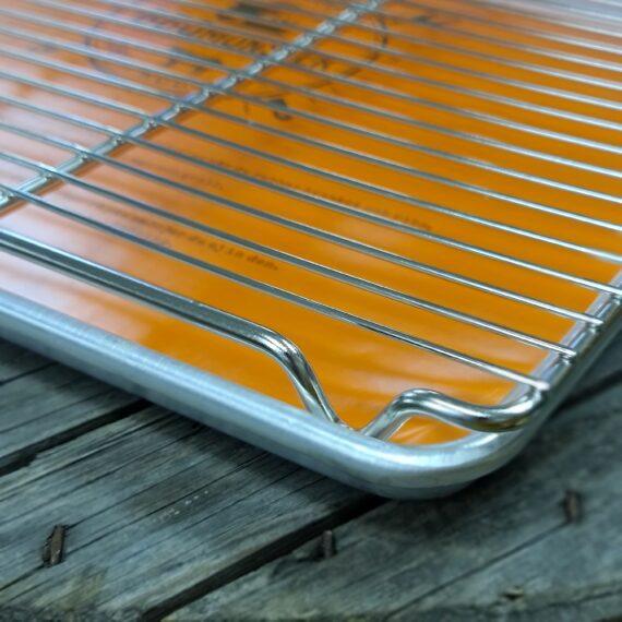 """Cooling rack pro kit Svalningsgaller + BBQ alu bricka Kylskåpsanpassade storlek Ugnsanpassad storlek BBQmonsters populära bricka i obehandlad aluminium i kit med Cooling rack i rostfritt stål - låt köttet vila effektivt på detta galler Detta är ett pro kit innehållandes ett väldigt rejält cooling rack i rostfritt stål samt en bricka i aluminium som passar helt perfekt med avsvalningsgallret på sina """"axlar"""". Med ett cooling rack (svalningsgaller) skapar du luft under köttet och processen med att vila ner köttet (ex. brisket eller pulled pork karré) ned mot 70 grader går snabbare. Safter som droppar ut landar snyggt i aluminium tråget. Att låta köttet vila och tappa grader kan vara skillnaden mellan bra och perfekt! Under vilan fördelas värmen jämnt, köttet återtar en del safter och muskelfiber går från anspända till avslappnade. Ju längre tillagningstid desto längre vila. Rådet är att du låter köttet vila i slaktarpapper placerat på detta galler. (Fördelen med slaktarpapper framför folie är att slaktarpapper andas och förhindrar att temperaturen stiger under vilan).  Mått på alubrickan: 46 x 33 x 2,5cm"""