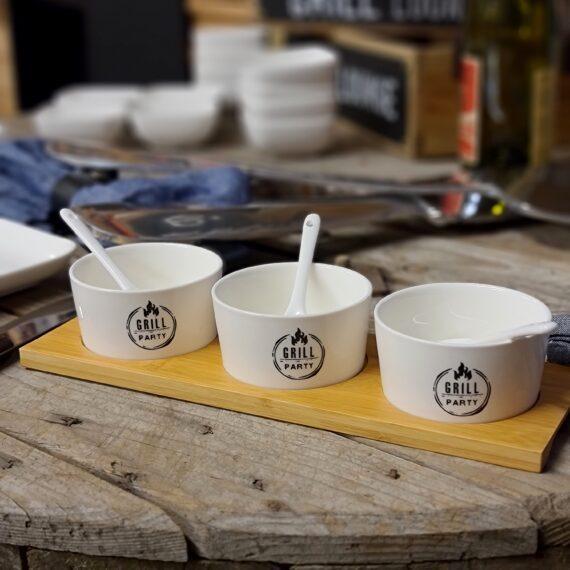 """Skålar och skedar i keramik Kommer på träbräda """"Grillparty"""" - Perfekt för att duka fram sås och dip Snygga småskålar med tillhörande skedar för grillfesten och uteköket Dessa glaserade skålar och skedar ser allmänt fräscha ut i skrud av vitt ståendes på en träbräda med frästa hål för en stabil servering. På utsidan av skålarna finns ett tryck som berättar vad det handlar om: Grillparty! (ganska praktiskt ifall någon helt skulle tappa det en blöt kväll;)) Skålarna som ingår är 3 till antalet och grillparty skålarna tåler diskmaskin, inte en helt oviktig detalj klocka 02:45. MÅTT: diameter 8,5cm kanten är 4cm hög. Så passa på att duka snyggt i uteköket och säkra en fräsch BBQlifestyle som inte lämnar någon oberörd. Ute efter aluminium brickor och tallrikar? https://bbqmonster.se/produkt-kategori/aluminium-brickor-bbq/"""