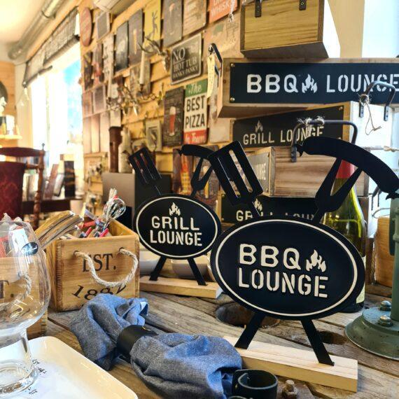 """Bordsdekor BBQ / Grill-lounge snyggt i köket eller uteköket av trä och metall 30cm höga Detta är en bordsdekor av trä och metall. Bordsdekorationen finns i två olika versioner som ger följande budskap: Grill Lounge BBQ Lounge Passar perfekt i uteköket och grillhörnan. Mysigt i stugan och grillhörnan inredning för en """"Lodge lifestyle"""" och """"Cottage lifestyle"""" BBQmonster har lanserat ett utvalt koncept av prylar som ryms inom begreppen BBQlifestyle, Lodge lifestyle och Cottage Lifestyle, en växande trend är nämligen att vi söker oss mot en inredning som skall ge oss lugn och gemyt. För många är sannolikt den ultimata målbilden en spartanskt inredd stuga, gärna med träväggar, öppen spis och en lurvig fäll på golvet. I dessa två koncept skall BBQmonster försöka hitta guldkornen (eller silver eller trä...) som symboliserar och skapar känslan av mysfaktor hög. Butiken i Ödåkra är i sig själv inredd med liggande träpanel och inredning som skall skapa en skön känsla, Det är utifrån kunders frågor kring inredning som BBQmonster fick idéen att utöka med dessa Lodge Lifestyle och Cottage Lifestyle. Planen är inte att göra om BBQmonster till en inredningsbutik, utan fokus kommer fortsatt vara på GRILL och BBQ - men då livsnjuteri vid grillen är starkt närbesläktat med livsnjuteriet som sker under en weekend i stugan, i fjällen eller kanske i ditt hem som du format utefter att få känslan av en timmerstuga, jaktstuga eller någon annan målbild som du ser för ditt inre."""