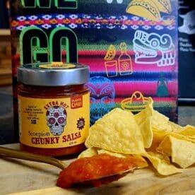 Chunky salsa - Scorpion Moruga chili - sting och hetta, perfekt till tortillas och tacos - Ekologisk Skånsk Chili Chunky salsa med rötterna i Skånska myllan, närmare bestämt i världsmetropolen Asmundtorp, känn på den världen! Denna Chunky salsa med underbar fruktighet från mycket heta Scorpion moruga chili görs på deras egenodlade och obesprutade chilis, även koriandern är egenodlad. Tomaterna kommer från Skåne. Produktionen sker utan konserveringsmedel men tack vare en värmebehandling är hållbarheten mycket god. Chunky salsa Scorpion moruga är lurigt röd i färgen och ger ett mycket fruktigt svar när den landar på tungan. Chilistinget är starkt (men ändå ingen bedövare som denna chilisort ibland kan vara). Den värmer och hettar en del men det följer inte med ned i magen utan håller sig i munnen. Fruktigheten från denna lilla våldsamma chili är fantastisk, lite som en habanero på steroider. Koriander, lime. äpple och en lätt sälta kompletterar den fina sötman som kommer från ananas - och därmed har vi en välsmakande, het, chunky salsa som inte lämnar någon smaklök oberörd. Använd denna Chunky salsa Scorpion Moruga som dip till tortillachips eller sleva ut den över dina tacos - go loco! 225 ml