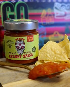Chunky salsa - Tomat Habanero - perfekt till tortillas och tacos - Ekologisk Skånsk Chili Chunky salsa med rötterna i Skånska myllan, närmare bestämt i världsmetropolen Asmundtorp, känn på den världen! Denna Chunky salsa med smak av fruktig Habanero görs på deras egenodlade och obesprutade chilis, även koriandern är egenodlad. Tomaterna kommer från Skåne. Produktionen sker utan konserveringsmedel men tack vare en värmebehandling är hållbarheten mycket god. Chunky salsa Tomat Habanero är fint röd i färgen och ger ett mycket fruktigt svar när den landar på tungan. Chilistinget är medelstarkt (vi pratar trots allt om habanero) och värmer fint samtidigt som den underbara höga fruktigheten från habanero smörjer tungan med ett djup som nästa påminner om mogen banan. Koriander, lime. äpple och en lätt sälta kompletterar den fina sötman som kommer från ananas - och därmed har vi en välsmakande, het, chunky salsa som inte lämnar någon smaklök oberörd. Använd denna Chunky salsa tomat habanero som dip till tortillachips eller sleva ut den över dina tacos - go loco! 225 ml