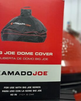 """Regnskydd """"Dome cover"""" Ett väderskydd för inbyggd kamado Kamado BIG JOE Regnskydd, väderskydd för Kamado BIG Joe (alla versioner) och andra 61cm kamados. ÄNTLIGEN säger alla som byggt utekök och däri byggt in sin Kamado - detta är ett """"dome cover"""", alltså ett skydd som täcker toppen på din inbyggda kamado. Skydda din röda skönhet från regn, snö eller sandstormar - vem vet vad som händer här näst. Med detta skydd maximerar du livslängden och inte minst lika viktigt - håller din Kamado redo för grillning året runt. Ett """"dome cover"""" skiljer sig från de andra regnskydden eftersom att det endast täcker själva locket och skorstenen på din inbyggda kamado. Detta regnskydd är skräddarsytt för Kamado BIG JOE och passar både version 1, version 2 och version 3. Gissningsvis passar det även samtliga andra kamados i storlek kring 61 cm i grillyta, exempelvis Big Green Egg XL med flera. På baksidan av skyddet finns det ett ventilationshål (se bild) och tanken är att skapa ett nyttigt flöde av luft för att förhindra en allt för fuktig miljö på grund av kondens. Det finns två snabbfästen för att säkert kunna förankra regnskyddet. Vid skorstenen finns ett handtag för att förenkla hanteringen."""
