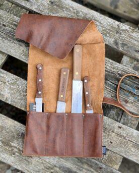 Knivrulle - brun premium i mjukaste läder - Brickwalls and Barricades- knivförvaring av klass En knivrulle av det mjukaste och mest följsamma läder som du kan fantisera om. Häri bor dina knivar snyggt och praktiskt- ett hantverk från Holland. En knivrulle av brunt läder som bara blir snyggare och snyggare med tiden. Knivrullen passar i sin stil, kvalitet och komfort alla som gillar premiumprodukter - du kommer inte hitta något mer naturligt vackert läder än detta buffelläder. Färgen är brun med naturliga variationer som skapar liv och naturligt mönster. Skinnet är följsamt och mjukt från dag 1 och BBQmonster vågar lova att du knappast kommer att hitta en snyggare knivrulle att förvara dina knivar i. Knivrullen rymmer 4 knivar och har en lång rem som du sveper runt den ihoprullade knivrullen
