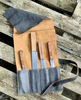 Knivrulle - premium i mjukaste läder - Brickwalls and Barricades- knivförvaring av klass En knivrulle av det mjukaste och mest följsamma läder som du kan fantisera om. Häri bor dina knivar snyggt och praktiskt- ett hantverk från Holland. En knivrulle av svart läder som bara blir snyggare och snyggare med tiden. Knivrullen passar i sin stil, kvalitet och komfort alla som gillar premiumprodukter - du kommer inte hitta något mer naturligt vackert läder än detta buffelläder. Färgen är Svart med naturliga variationer som skapar liv och naturligt mönster. Skinnet är följsamt och mjukt från dag 1 och BBQmonster vågar lova att du knappast kommer att hitta en snyggare knivrulle att förvara dina knivar i. Knivrullen rymmer 4 knivar och har en lång rem som du sveper runt den ihoprullade knivrullen