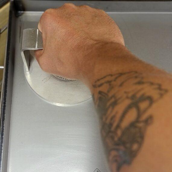 Smashburger järn BBQmonster - en 13cm burger smasher i 6mm rostfritt stål - made in Sweden Burger Smasher Smasher Smash burger tool Smash järn Smashburger järn producerat i Sverige. Gjort av i rostfritt stål för att du skall kunna slänga det i diskmaskinen efter att smashat feta bollar av grainfed black angus färs. Smashburgers är en fortsatt populär tillagningsmetod för hamburgare som går ut på att en köttbulle som snabbt bränns av på het stekplatta bankas ut med en välriktad högerkrok. När smashburger inte längre kan ses som en trend utan som den nya standarden för att göra fina burgare så kändes självklart att BBQmonster skulle skaffa sig en egen smasher, en rejäl smasher, inte den lyxigaste och mest skinande blanka smasher men en mycket rustik och tålig sådan - i rätt storlek även för dig som önskar större burgare. Den lokala smeden fick uppgiften att ta fram sitt bästa rostfria material, sätta på ett handtag som rymmer även en manshand klädd i en värmetålig handske och även bränna in BBQmonster logo - så vi vet var den kommer ifrån. Så här är den - smash järnet från BBQmonster. Diameter 13cm, vikt 800 gram Kombinera gärna med BBQmonsters stekbord