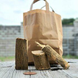 """Chunks - Apelsin - Rökträ - Rökved - perfekt för gris, veg, fågel och fisk Apelsin trä som smokewood - Chunks är beskrivning av en knappt knytnävsstor träbit - en vedklabb sågad i ungefär 4 bitar och kluven 1 eller 2 gånger. Fördelen med chunks före wood chips och rökspån är att en trä-chunk inte brinner upp medans du stänger locket och tar en sipp av ölen, - detta trä kan producera rök under ett par timmar eller mer. Detta är apelsin chunks (rökträ av apelsin eller smokewood av apelsinträd) som till ca största del är avbarkat. Barken skadar inte men väger mindre och skapar inte lika mycket rök och smak, varför många föredrag trä med stor del avbarkat. Vissa rykten säger att att Ozzy Osbourne inspirerades av detta när han spelade in låten """"bark at the moon"""" (nä nu skojar vi). Om du är ute efter att röka köttet och köra low & slow är det utan tvekan denna storlek du bör välja. Sikta på att tillföra rök under åtminstone de tre första timmarna. Det är då som köttet är som mest mottagligt för rök. Faktum är att det framför allt är när köttet är riktigt kallt (eller fruset) som mest rökpartiklar fastnar på ytan (testa till exempel att röka lax frusen!). När köttet blir torrt på ytan slutar köttet till stor del att ta emot röken. Det är i detta läget som det kan vara aktuellt att använda en sprayflaska för """"slather"""" (se denna artikel) Apelsin, är relativt nytt som rökträ och rökved. Doften är inte citrus så som man kanske kan inbilla sig men det är en mjuk """"rund"""" och behaglig rök som definitivt inte gör ont någonstans. Levereras i en fullpackad pappåse om 6liter (vikt varierar beroende på träslag men ca 1,9kg för detta träslag) Om att använda trä för att skapa rök: Blött trä släcker delvis glöden från kolen och skapar oftast en smutsigare rök. Målet när du tillför rökträ är att skapa en fullständig förbränning där röken är klar och fin, inte tjock och mullrande. Thin blue smoke pratar det stora landet i väster om och även om det inte alltid är blå rök som lämnar skorstene"""
