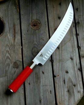 """Red Spirit """"Hektor"""" - Butcher knife av Tyskt rostfritt kolstål - proffskniv från F.Dick - grundat 1778. Butcher knife, Slaktkniv, Delningskniv från anrika F.Dick som grundades redan 1778. Knivtypen sett till formen påminner om en Breaking knife även kallat Cimeter kniv vilket är en styckningskniv med kurvat (böjt) långt blad, likt en sabel. Knivtypen används för att stycka upp större köttstycke i mindre bitar. Även den största bit högrev styckas med enkelhet upp i kuber med denna bländande blanka Breaking knife. Att bladet är kurvat (böjt) gör att du med en gungande rörelse med enkelhet skär igenom även de största styckdetaljerna. Delningsknivens totala längd är ca 40 cm, fördelat på ett handtag på 14cm och ett 26 cm långt, styvt blad med sylvass egg. Knivarna används professionellt av både styckare och slaktare. Fokus på användarvänlighet, enkelhet att rengöra och ergonomi ligger i fokus. Skaftet ger ett bra grepp och är enkelt att rengöra. Handtaget passar både höger- och vänsterhänta. Red Spirit Hektor är gjorda för att kunna användas professionellt. Både skaft och blad är helt fritt från mikroporer vilket gör att både blad och handtag går att får helt rent och desinficerat. Made in Germany av tyskt kvalitetsstål med följande egenskaper: Kolstål med blandning X50CrMoV15 Hårdhet 56° HRC vilket är ett relativt mjukt stål - något som gör att du själv enkelt kan hålla din kniv vass. Längd på bladet: 26 cm Längd på skaftet: 14 cm"""