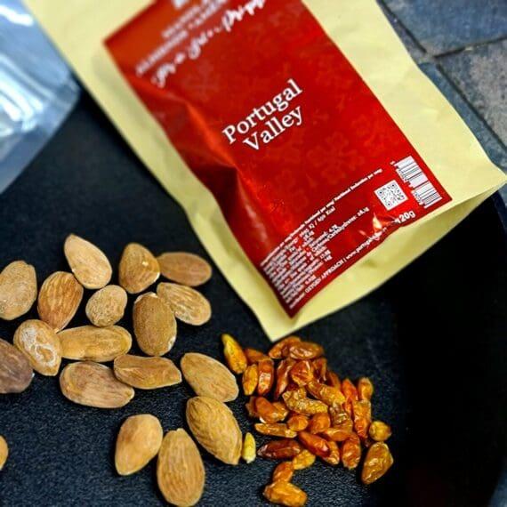 """Rostade mandlar från Portugal: Piri-piri eller havssalt - svårt beroendeframkallande proteinrikt snacks fyllda med nyttiga fetter! Satan. det var bra tryck i dem! Ja, det är faktiskt en direkt ljudupptagning från ett samtal med grannen Lasse (som för övrigt vill vara anonym). Jo, och Lasse har rätt, Mandlar I den röda påsen med Piri-piri från Portugal skall inte förväxlas med den silvriga påsen som innehåller Portugisiska mandlar saltade med gott havssalt (en produkt som Portugal är lokala världsmästare på). I jakten på den optimala dad-bodden eller mum-bodden så skall du välja snacks med omsorg. Välj bort socker, välj snacks med mycket protein och mycket fett. Detta mättar istället för att trigga ytterligare en och ytterligare en näve med """"blandgodis"""". Salta mandlar från Portugal och starka chili Mandlar kryddade med Piri-piri är perfekta kompanjonen i väskan, i golfbagen, i jackfickan när hungern smäller till. Lika given är produkten upphälld i små söta skålar framställda framför ditt fina IPA-glas i din mancave. High protein, low carbs - snacks Nettovikt 120 gram"""