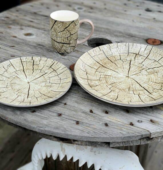 """Tallrik """"timber"""" 28cm i 6pack - motiv av en en timmerstock i genomskärning Mysigt i stugan och grillhörnan inredning för en """"Lodge lifestyle"""" och """"Cottage lifestyle"""" Tallrik, mattallrik 28cm, med ett unikt motiv - en timmerstock i genomskärning! Säljs i paket om 6st i varje. Duka snyggt och med en rustik stil med denna tallrik med motiv av en timmerstock. BBQmonster har lanserat ett utvalt koncept av prylar som ryms inom begreppet Lodge lifestyle och Cottage Lifestyle, en växande trend är nämligen att vi söker oss mot en inredning som skall ge oss lugn och gemyt. För många är sannolikt den ultimata målbilden en spartanskt inredd stuga, gärna med träväggar, öppen spis och en lurvig fäll på golvet. I dessa två koncept skall BBQmonster försöka hitta guldkornen (eller silver eller trä...) som symboliserar och skapar känslan av mysfaktor hög. Butiken i Ödåkra är i sig själv inredd med liggande träpanel och inredning som skall skapa en skön känsla, Det är utifrån kunders frågor kring inredning som BBQmonster fick idéen att utöka med dessa Lodge Lifestyle och Cottage Lifestyle. Planen är inte att göra om BBQmonster till en inredningsbutik, utan fokus kommer fortsatt vara på GRILL och BBQ - men då livsnjuteri vid grillen är starkt närbesläktat med livsnjuteriet som sker under en weekend i stugan, i fjällen eller kanske i ditt hem som du format utefter att få känslan av en timmerstuga, jaktstuga eller någon annan målbild som du ser för ditt inre. Här har du ett sådan objekt: en tallrik av keramik med motiv föreställande en timmerstock Mått (cm): 28cm i diameter Vikt 1kg per styck Paketet innehåller 6stycken tallrikar"""