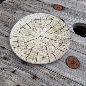 """Tallrik """"timber"""" 22cm i 6pack - motiv av en en timmerstock i genomskärning Mysigt i stugan och grillhörnan inredning för en """"Lodge lifestyle"""" och """"Cottage lifestyle"""" Tallrik, mattallrik 22cm, med ett unikt motiv - en timmerstock i genomskärning! Säljs i paket om 6st i varje. Duka snyggt och med en rustik stil med denna tallrik med motiv av en timmerstock. BBQmonster har lanserat ett utvalt koncept av prylar som ryms inom begreppet Lodge lifestyle och Cottage Lifestyle, en växande trend är nämligen att vi söker oss mot en inredning som skall ge oss lugn och gemyt. För många är sannolikt den ultimata målbilden en spartanskt inredd stuga, gärna med träväggar, öppen spis och en lurvig fäll på golvet. I dessa två koncept skall BBQmonster försöka hitta guldkornen (eller silver eller trä...) som symboliserar och skapar känslan av mysfaktor hög. Butiken i Ödåkra är i sig själv inredd med liggande träpanel och inredning som skall skapa en skön känsla, Det är utifrån kunders frågor kring inredning som BBQmonster fick idéen att utöka med dessa Lodge Lifestyle och Cottage Lifestyle. Planen är inte att göra om BBQmonster till en inredningsbutik, utan fokus kommer fortsatt vara på GRILL och BBQ - men då livsnjuteri vid grillen är starkt närbesläktat med livsnjuteriet som sker under en weekend i stugan, i fjällen eller kanske i ditt hem som du format utefter att få känslan av en timmerstuga, jaktstuga eller någon annan målbild som du ser för ditt inre. Här har du ett sådan objekt: en tallrik av keramik med motiv föreställande en timmerstock Mått (cm): 22cm i diameter Vikt 0.5 kg per styck Paketet innehåller 6stycken tallrikar"""
